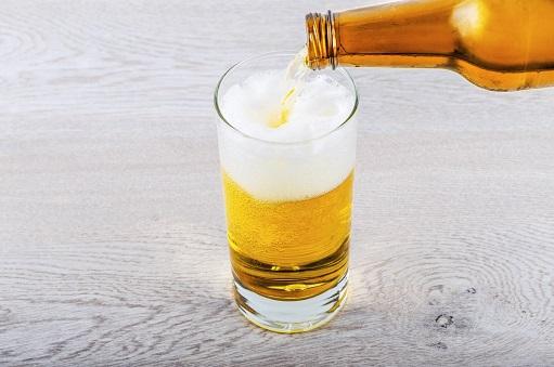 Vertiendo cerveza desde la botella hasta un vaso