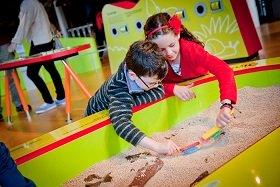 Dos niños jugando con arena en el museo nacional de Escocia en Edimburgo